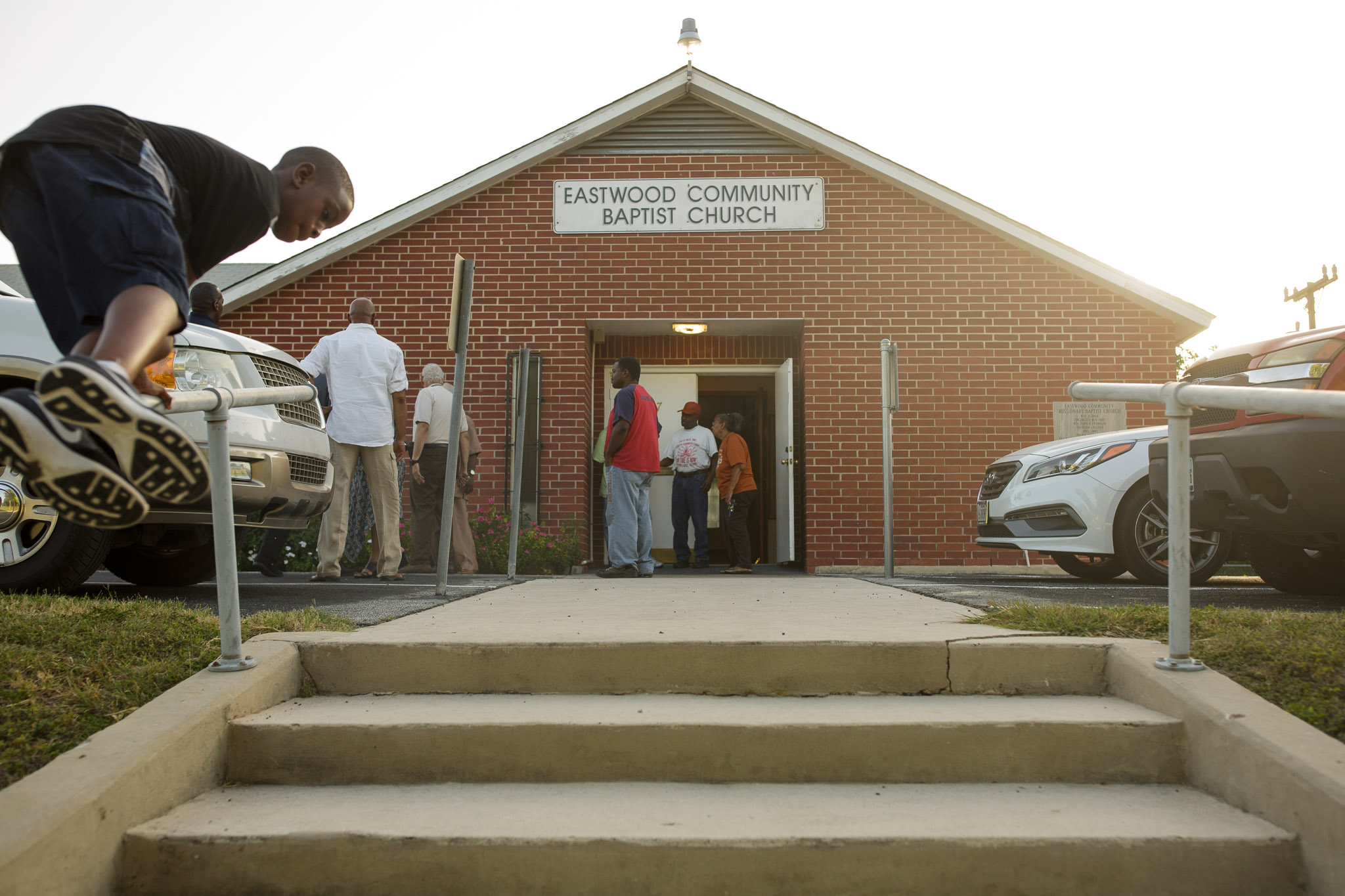 Following the community input meeting, residents of the area congregate outside Eastwood Community Baptist Church along Martin Luther King Drive. Photo by Scott Ball.