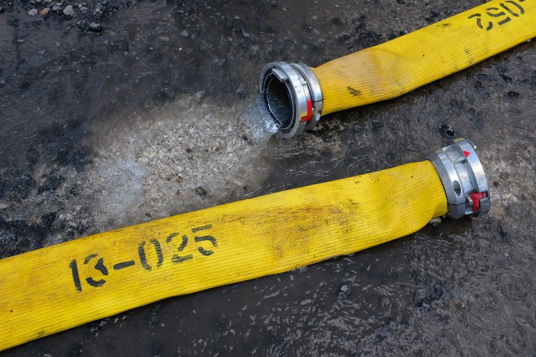 Water leaks out of a disjointed fire hose outside of the scene of the fire. Photo by Scott Ball.