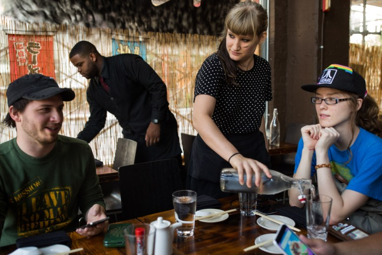 Waiter Tia Kelly (center) becomes interested in the conversation as she learns that the topic is Pokémon Go, Tia herself is a level 17 in the game. Photo by Scott Ball.