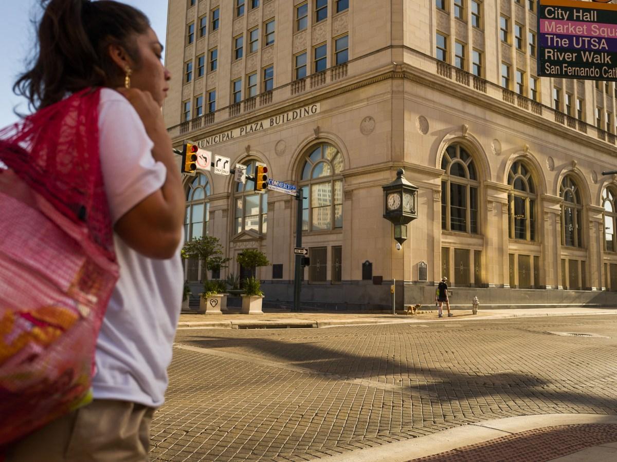 A woman walks by Main Plaza, a pedestrian-friendly area in downtown San Antonio.