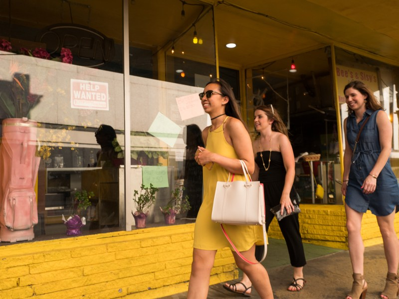 Downtown visitors walk beside longtime storefronts on Flores Street. Photo by Scott Ball.