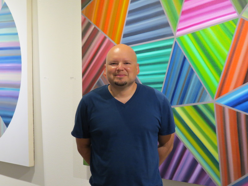 Louis Vega Treviño with his paintings at Musical Bridges Around the World Gallery. Photo by David S. Rubin.