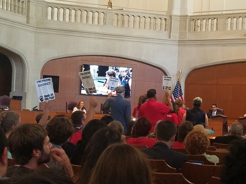 """Hotel union members hold signs that indicate the district in which they live and """"Hands Off Our Park."""" Photo by Iris Dimmick."""