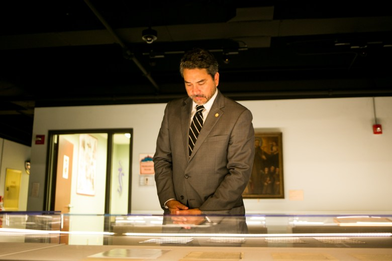 """Councilman Roberto Treviño (D1) looks at the """"Nuestra Historia, Our History: Spain in Bexar County"""" exhibit in the Federal Reserve Bank building. Photo by Kathryn Boyd-Batstone."""