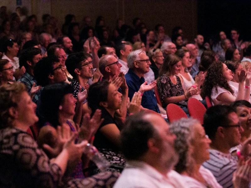Audience members applaud Auctioneer Robert Vogt as he recites a practice tongue twister. Photo by Kathryn Boyd-Batstone.