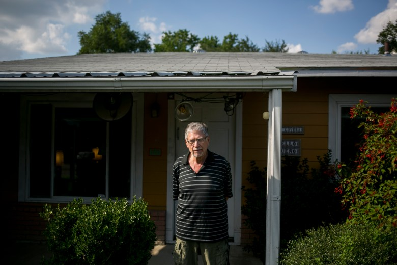 David Allen White stands in front of his white roofed house. Photo by Kathryn Boyd-Batstone.