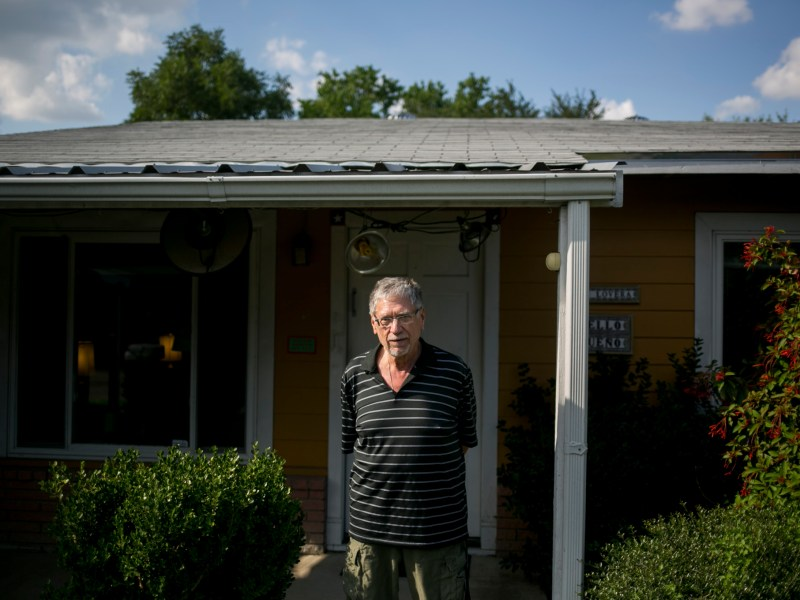 David Allen White stands in front of his home that received a white roof makeover.