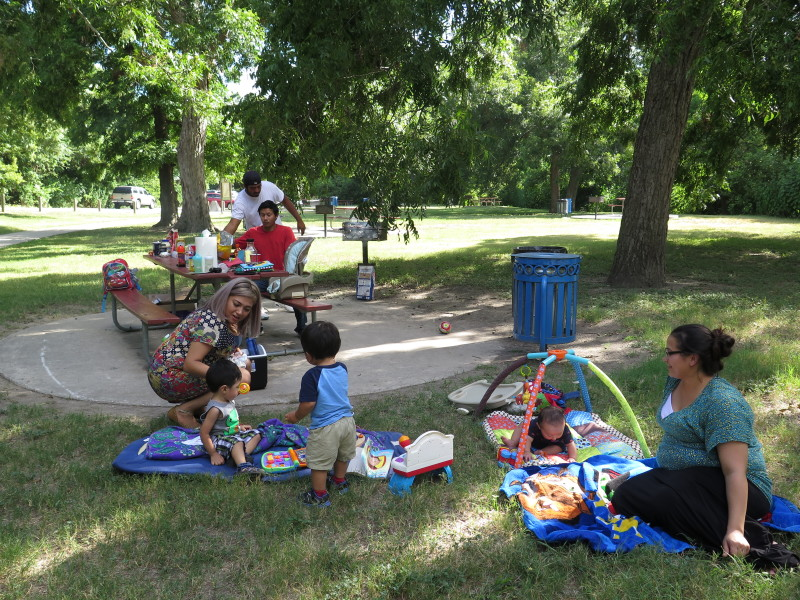 The Moncivais and Vicente families enjoy a picnic in the park. Photo by Rocío Guenther