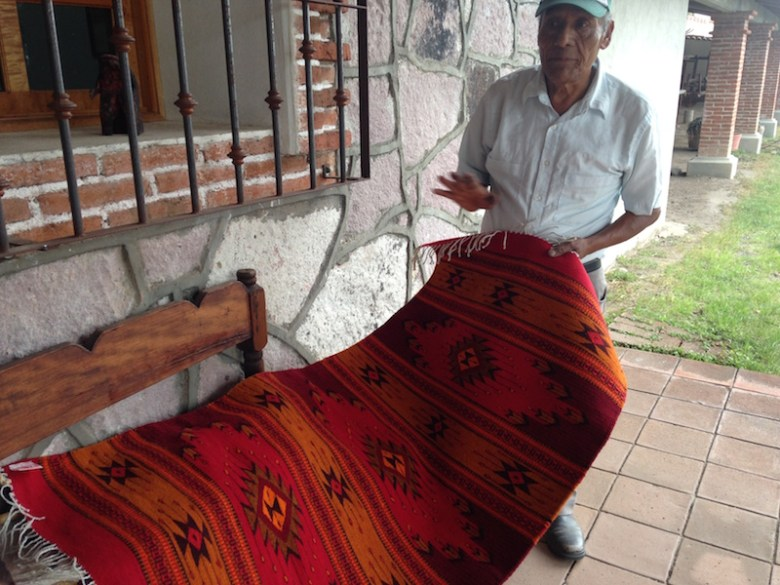 Benito shows off one of rugs. Photo by Kimberly Suta. Photo by Kimberly Suta.