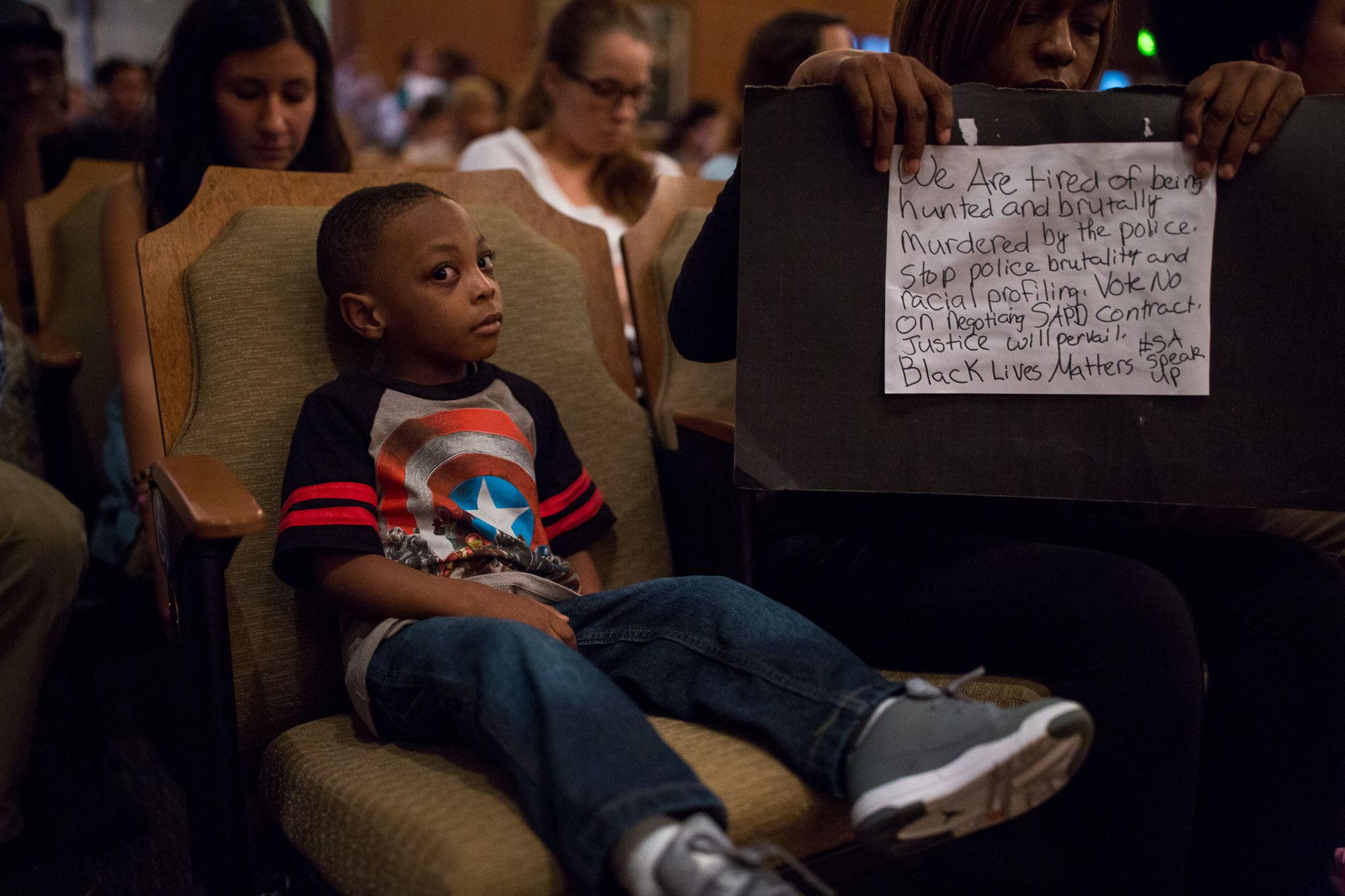 Joshua, 4, sits in a front row seat at the Citizens to be Heard meeting as his mother, Jala Minnfee holds a sign in protest of the San Antonio Police Union contract. Photo by Scott Ball.