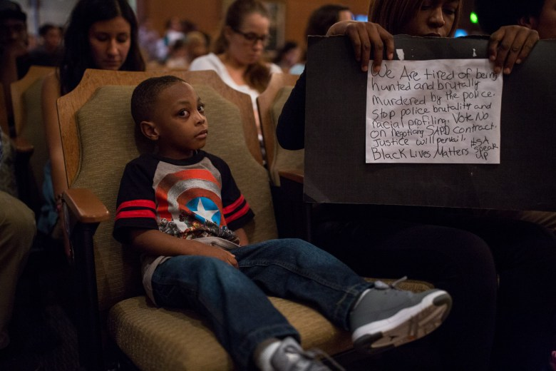 Joshua, 4, sits in a front row seat at the Citizens to be Heard meeting while his mother, Jala Minnfee holds a sign in protest of the San Antonio Police Union contract. Photo by Scott Ball.