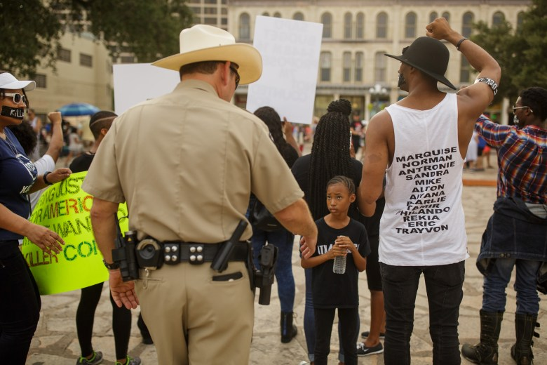 Naomi, 9, looks up at Alamo Ranger Security officer Kubena as he asks the protestors to remove themselves from Alamo property. Photo by Scott Ball.
