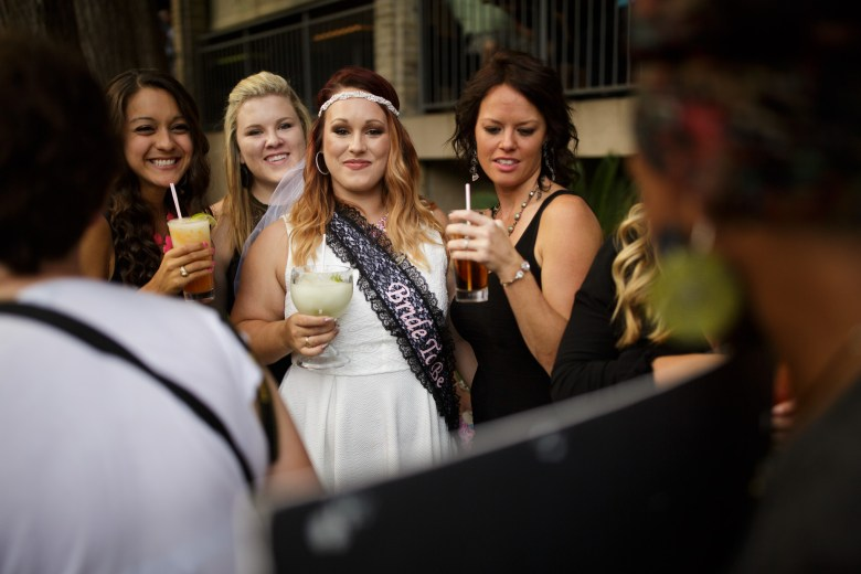 A bridal party observes the protestors as they pass by on the San Antonio River Walk. Photo by Scott Ball.