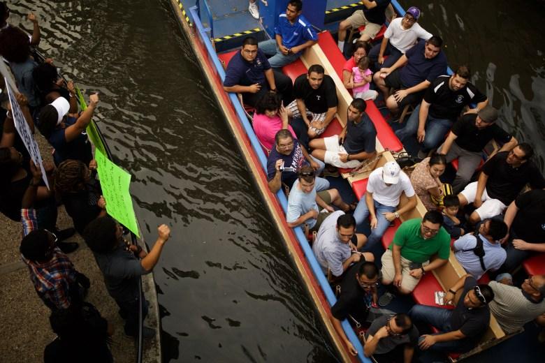 A riverboat tour passes as Black Lives Matter activists protest along the San Antonio River Walk. Photo by Scott Ball.