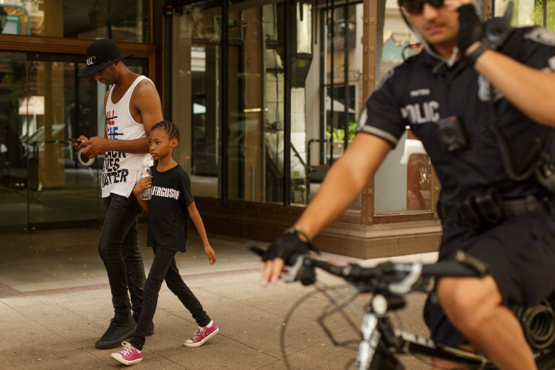 Mike Lowe walks along Houston Street with his daughter Naomi, 9, as San Antonio Police Officers follow along. Photo by Scott Ball.