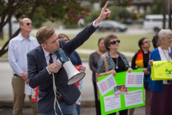 RAICES Executive Director and immigration attorney Johnathan Ryan points at the offices of the United States Immigration and Customs Enforcement (ICE) demanding for Children to be released from detention centers. Photo by Scott Ball.