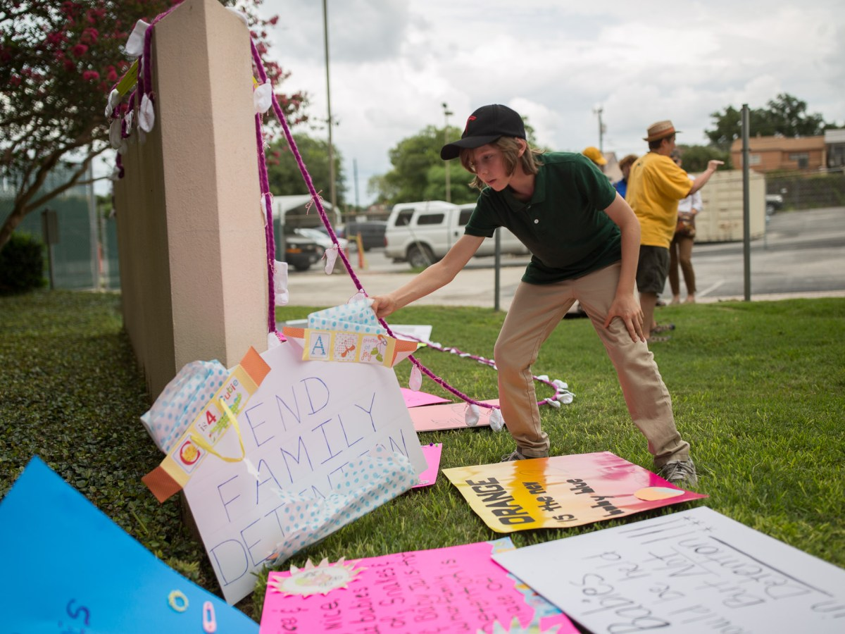 Benjamin, 12, carefully places a sign that reads 'End Family Detention' at the front sign of Protestors carry a long string of children's socks to the front of the United States Citizenship and Immigration Services building. Photo by Scott Ball.