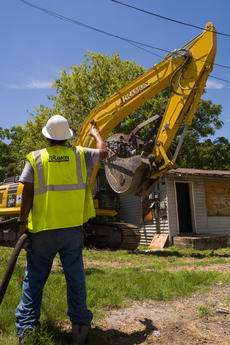A construction worker points to the operator of the machinery that will raze the Dillard house. Photo by Scott Ball.