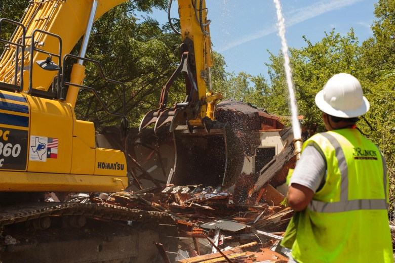 A worker sprays high pressured water onto the debris to prevent any possibility of ignition or fire. Photo by Scott Ball.