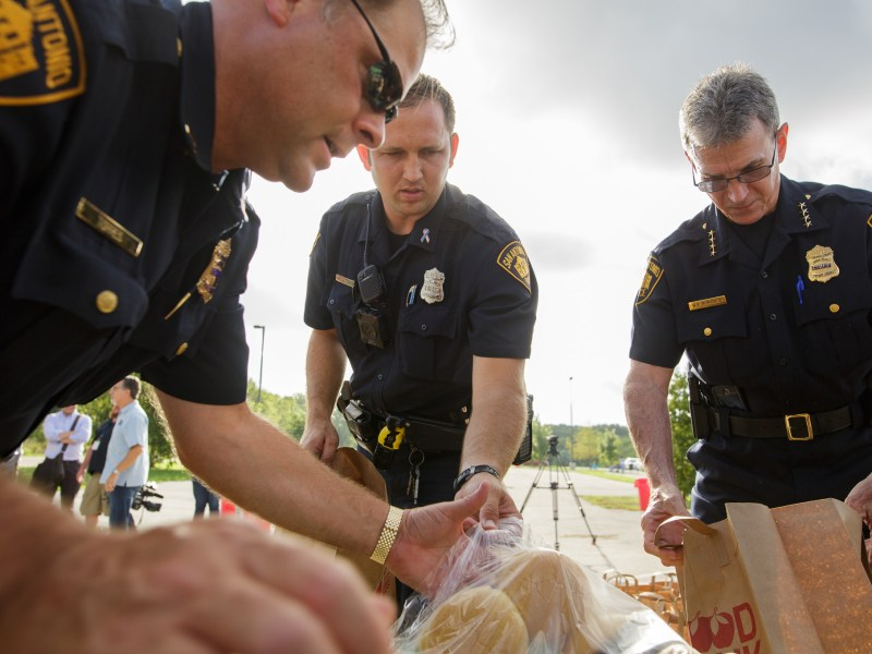 (left to right) San Antonio Police Capt. Troy Torres, Officer Kohlleppel, and Chief William McManus load paper bags with food for families in need. Photo by Scott Ball.