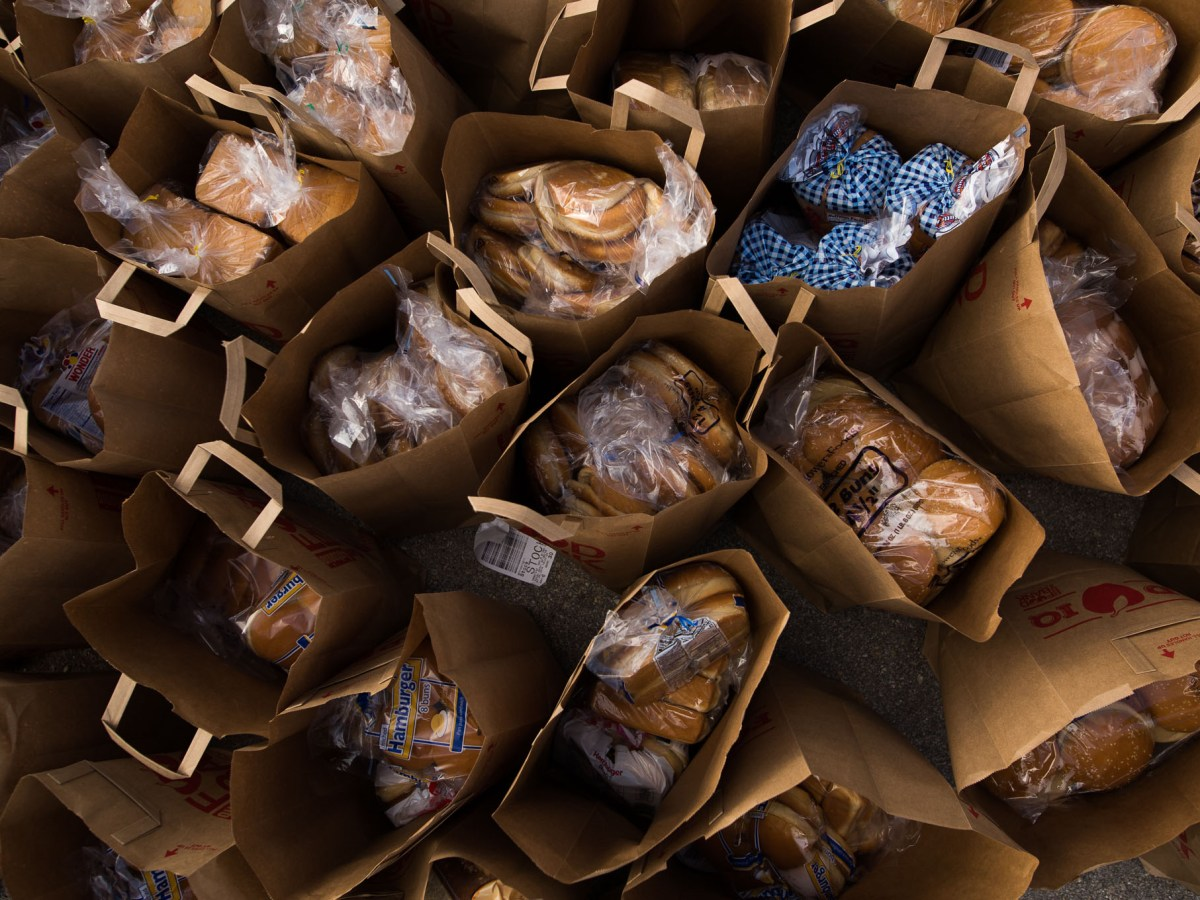 Bags full of groceries are bunched together before given out to needy families. Photo by Scott Ball.