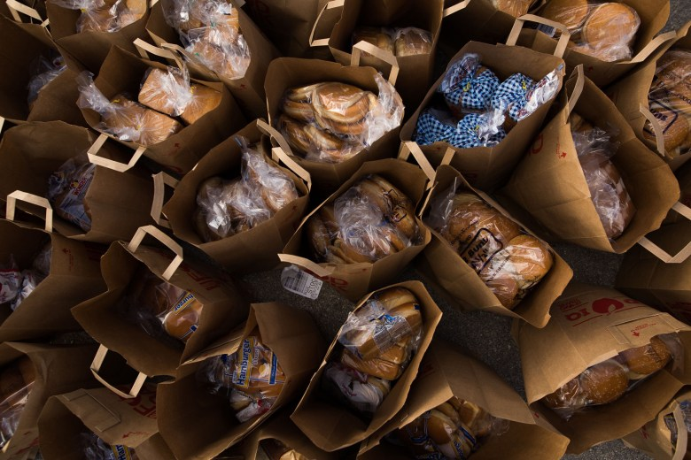 Bags filled with groceries are stockpiled before they are given out to families in need. Photo by Scott Ball.