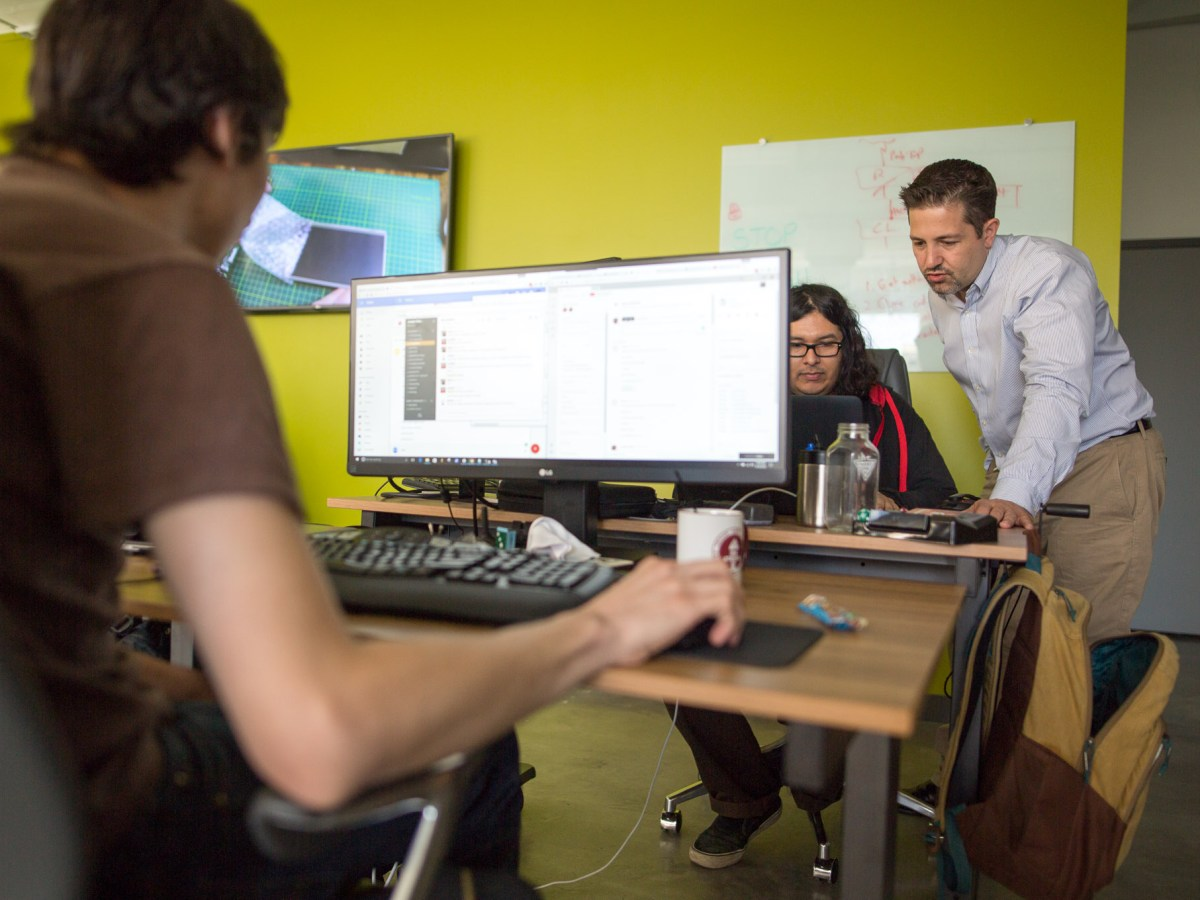 Jungle Disk CEO Bret Piatt works with Support Tech Juan Diaz in their new offices. Photo by Scott Ball.