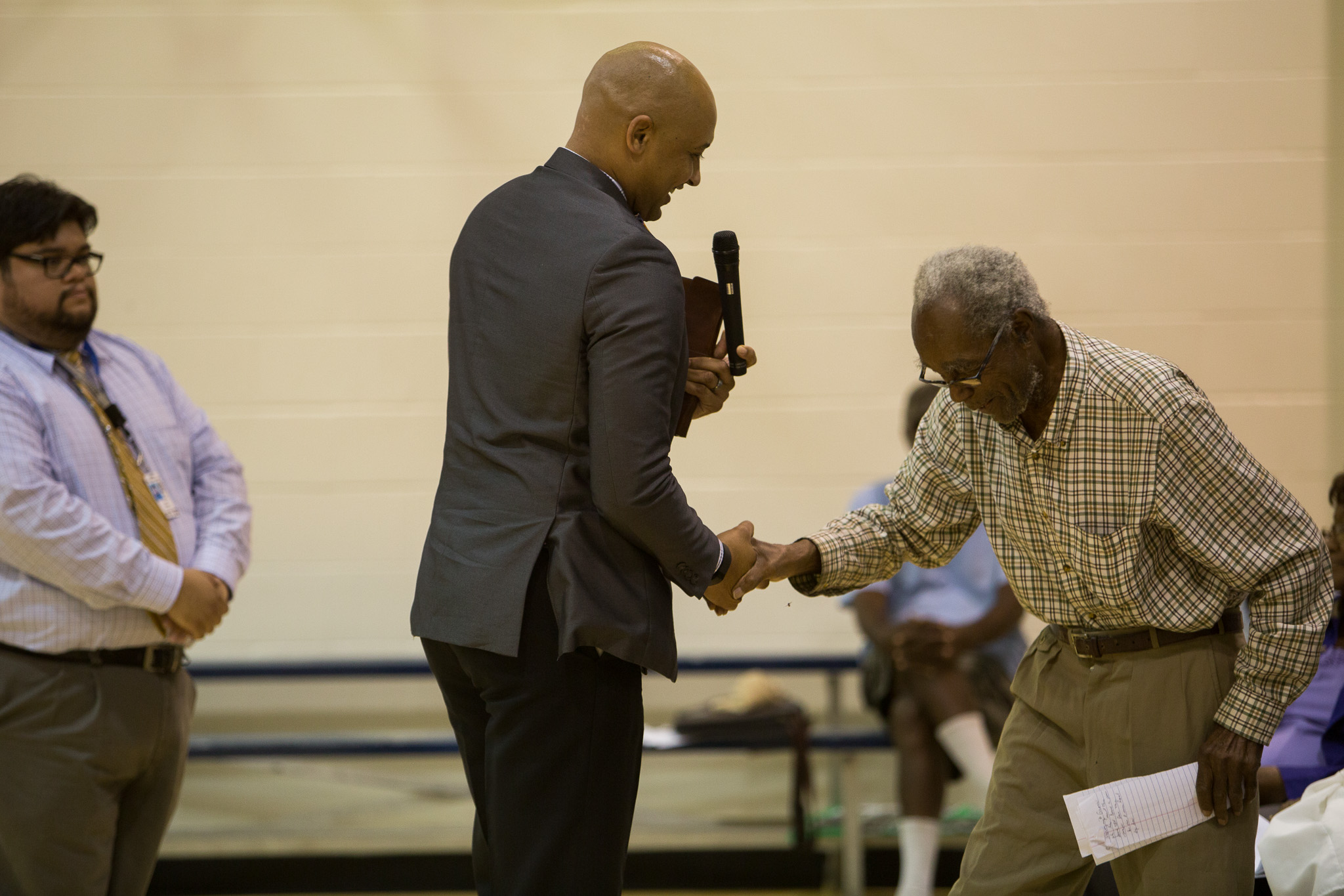 Councilman Alan Warrick helps community member Eugene Coleman to the podium. Photo by Scott Ball.