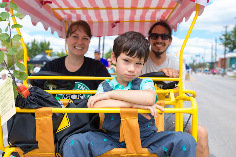 Judy and Marco Carmona ride their surrey bike with their son. Photo by Scott Ball.