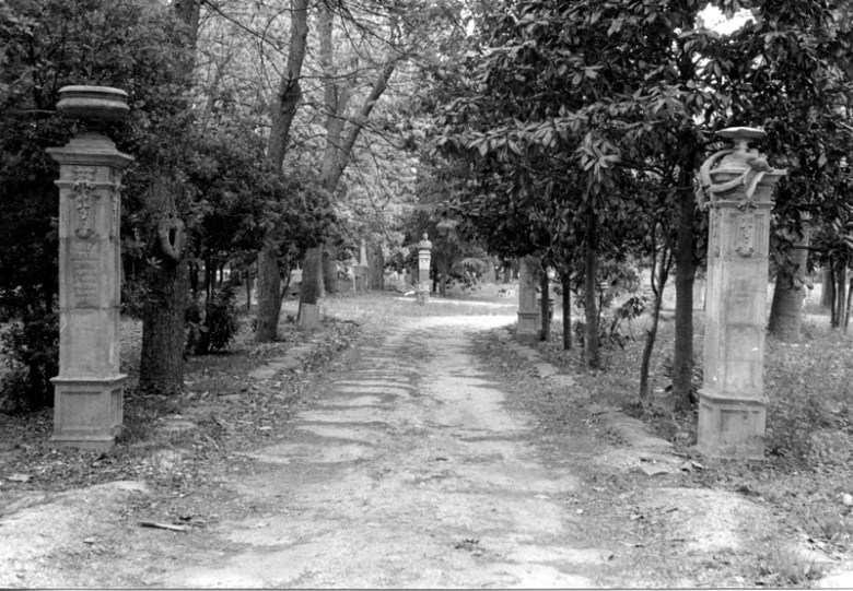 The same view, just inside the Hildebrand gate, 1980. The road is no longer maintained, and the pillars are decaying. The tower building behind the Díaz bust has been demolished. Photo by Elise Urrutia.
