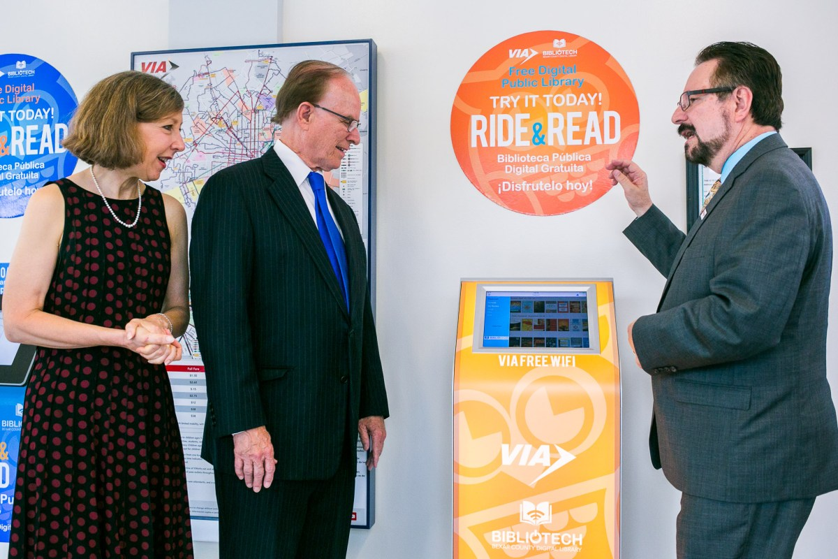 From left: BiblioTech Administrator Laura Cole, Bexar County Judge Nelson Wolff, VIA Metropolitan Transit President/CEO Jeffrey C. Arndt try out the new BiblioTech library kiosk. Photo by Kathryn Boyd-Batstone.