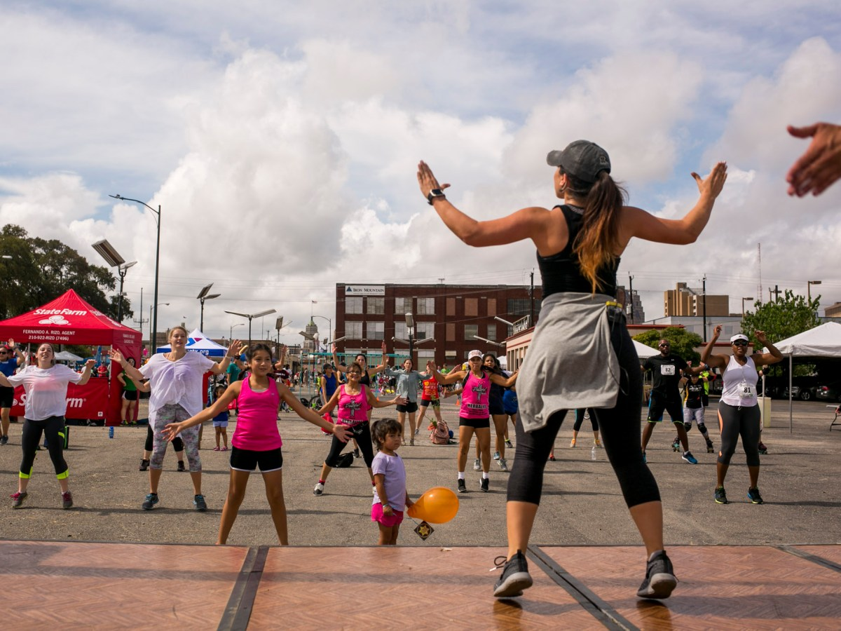 Zumba instructors lead participants through a warm up routine. Photo by Kathryn Boyd-Batstone.