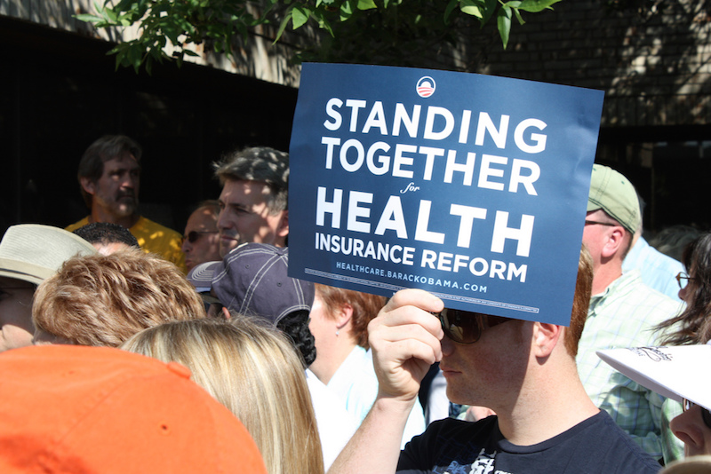 An advocate holds up a sign for health insurance reform. Photo courtesy of Flickr user Xavier.