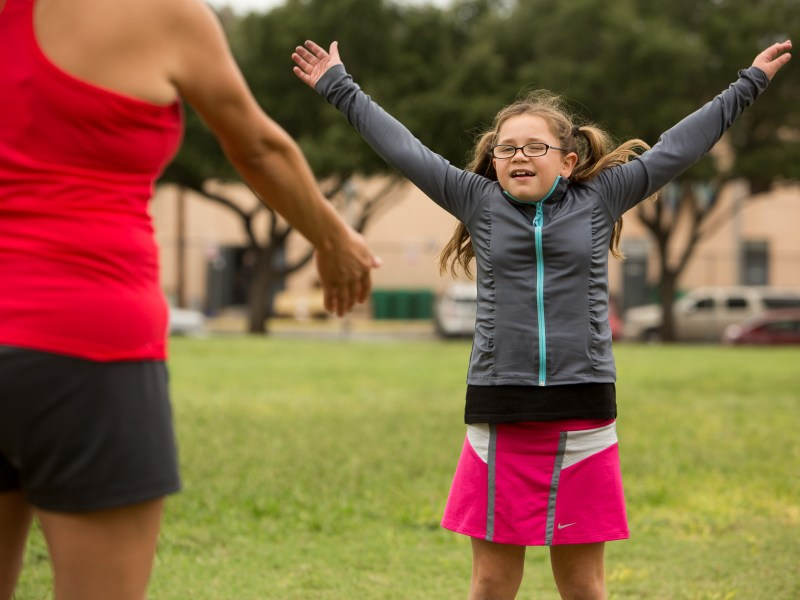 Ava, 8, twirls her arms as she warms up before running with classmates at Cambridge Elementary. Photo by Scott Ball.