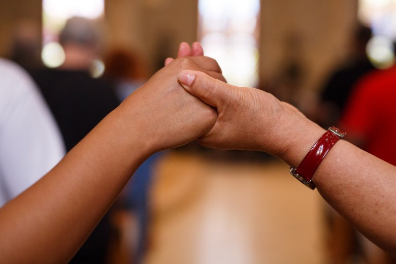 Church attendees hold hands as a prayer is said at San Fernando Cathedral. Photo by Scott Ball.