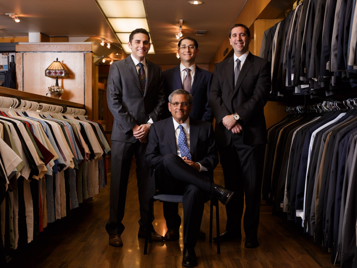 (left to right) Max, Mitchell, and Matt Penner surround Mark Penner in a group photograph at Penner's. Combined they have a total of 84 years experience working at the store. Photo by Scott Ball.