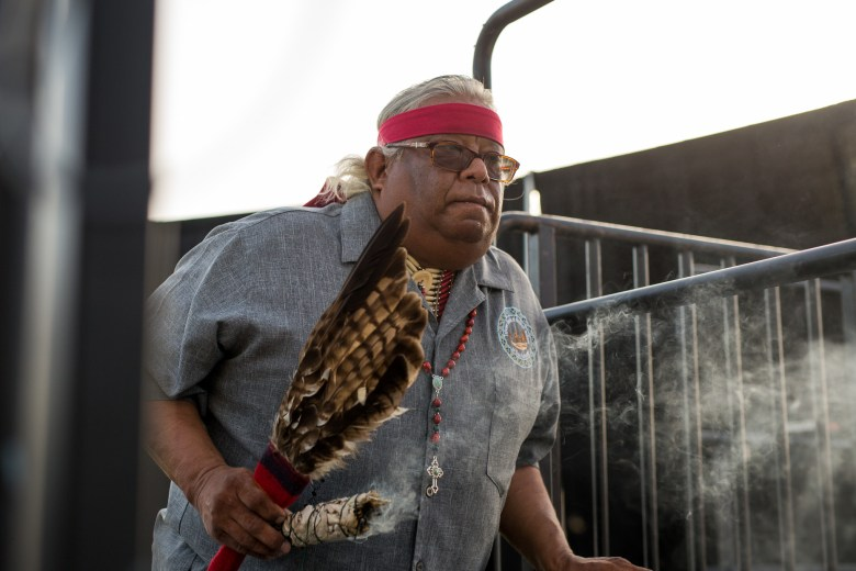 Epifanio Hernandez of the Tehuan Band of Mission Indians burns sage as he arrives to the stage. Photo by Scott Ball.