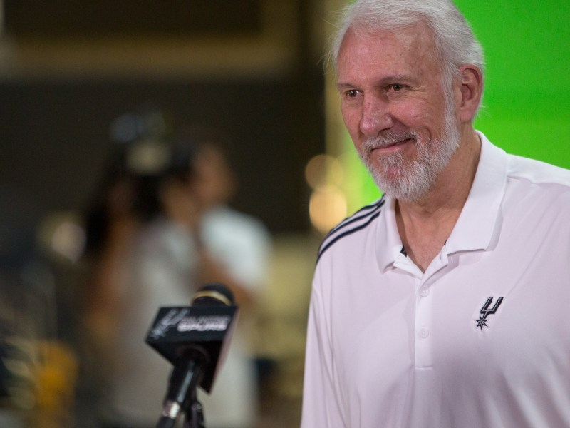 Spurs Head Coach Gregg Popovich smiles as he responds to a reporter. Photo by Scott Ball.