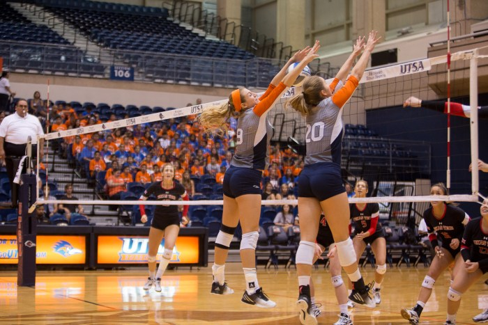 (left to right) Megan Slan and Jessica Waldrip jump high as a volley is blocked. Photo by Scott Ball.