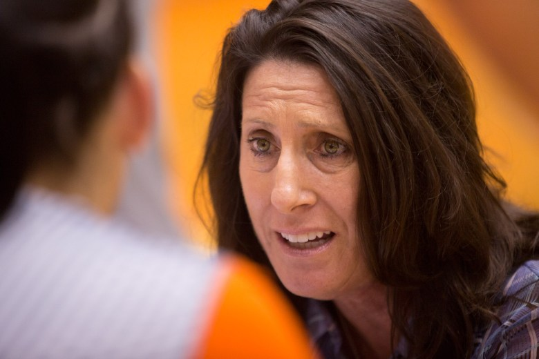 UTSA Volleyball Head Coach Laura Neugebauer-Groff sits and instructs a player on the sidelines. Photo by Scott Ball.