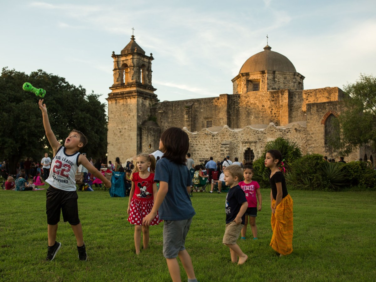 Children play in the green field facing Mission San José. Photo by Scott Ball.