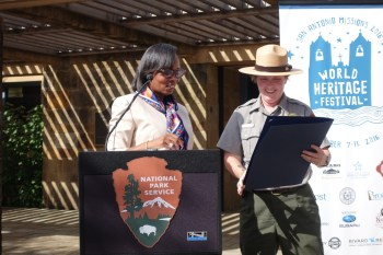 (From left): Mayor Ivy Taylor reads from an official City proclamation recognizing the World Heritage Festival as San Antonio Missions National Historical Park Superintendent Mardi Arce looks on. Photo by Robert Rivard.