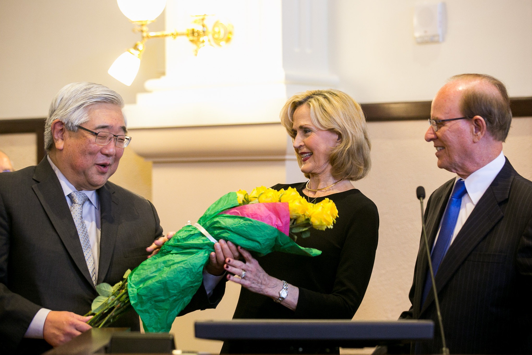 Children's Court Division & Programs Administrator Judge Peter Sakai presents Hidalgo Foundation Founder and President Tracy Wolff with a bouquet of The Yellow Rose of Texas. Photo by Kathryn Boyd-Batstone.