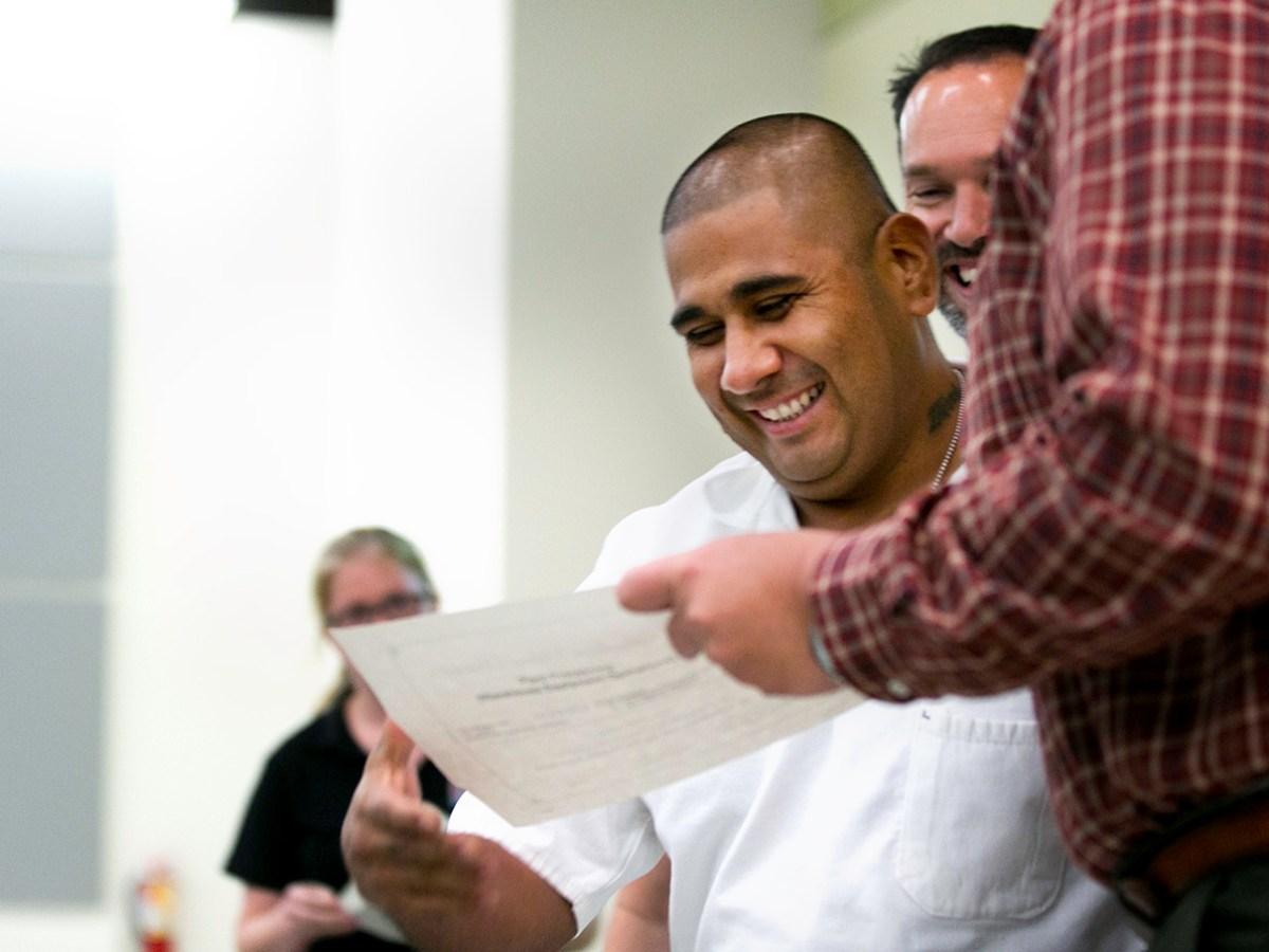 Samson Camion receives his graduation certificate. Photo by Kathryn Boyd-Batstone.
