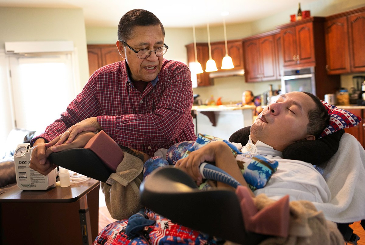 Julio Alvarado massages the muscles of his veteran son Luis Alvarado's hand to help them relax, Julio has been the primary caregiver for his son for over 5 years.