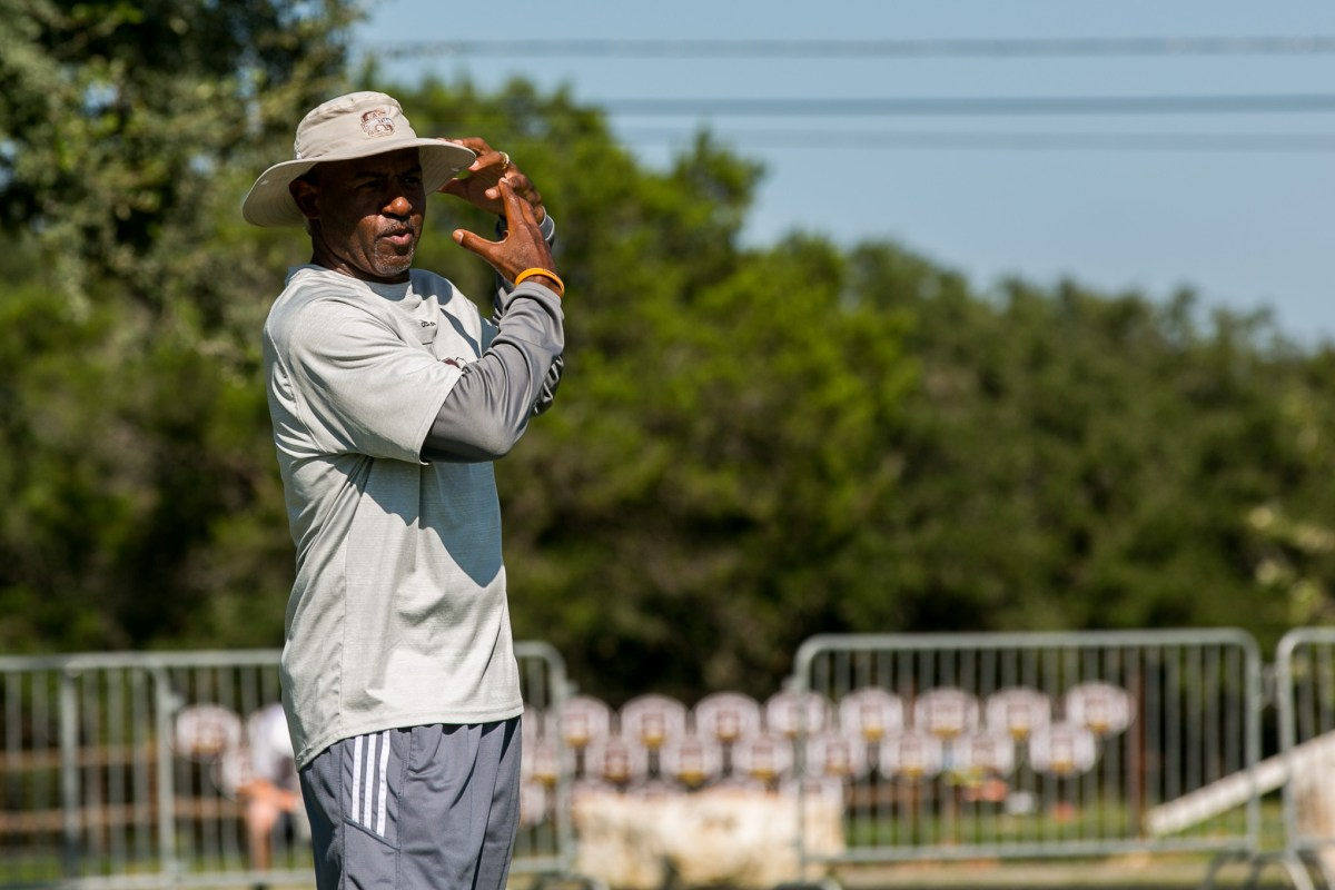 Henry Ellard reminds the San Antonio Christian football wide receivers about their form.