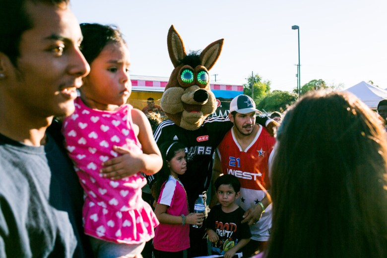 Families crowd the Spurs Coyote to get a picture.
