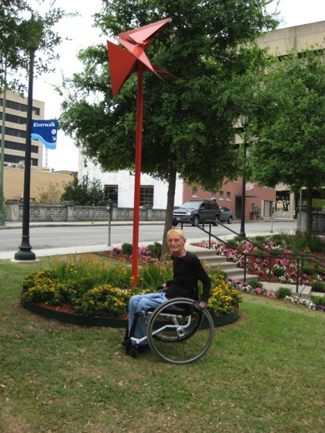 """Judy Babbitt in front of """"Red Bird,"""" a sculpture by local artist Mike Lance in Convent Street Pocket Park. Milton and Judy Babbitt's donation made the sculpture and installation possible."""