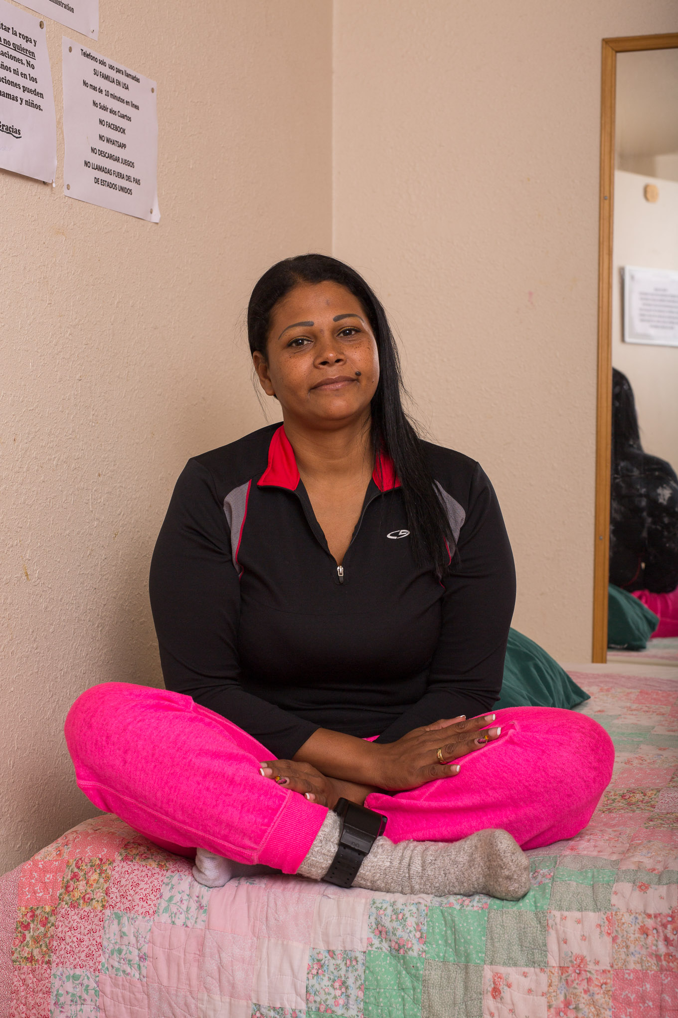 Maria Yanneth Lopez, 37, sits with her legs crossed on her temporary bed at Casa RAICES.