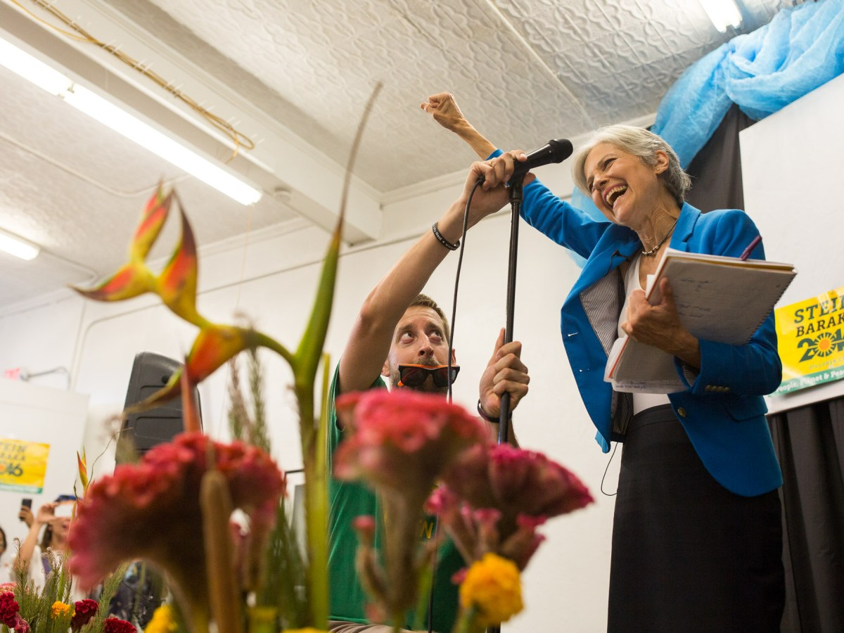 Green Party presidential candidate Dr. Jill Stein raises her fist as she appears in front of the crowd.